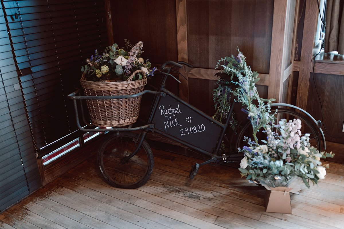vintage black bike with chalkboard sign that's filled with wedding flowers