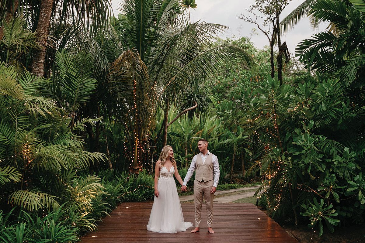 a bride and groom surrounded by tropical trees at The Sarojin in Khao Lak in Thailand