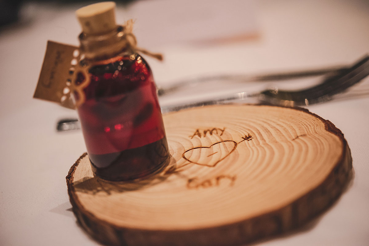 a slice of wooden log carved with Amy heart Gary and a small gift bottle with a cork filled with a red liquid