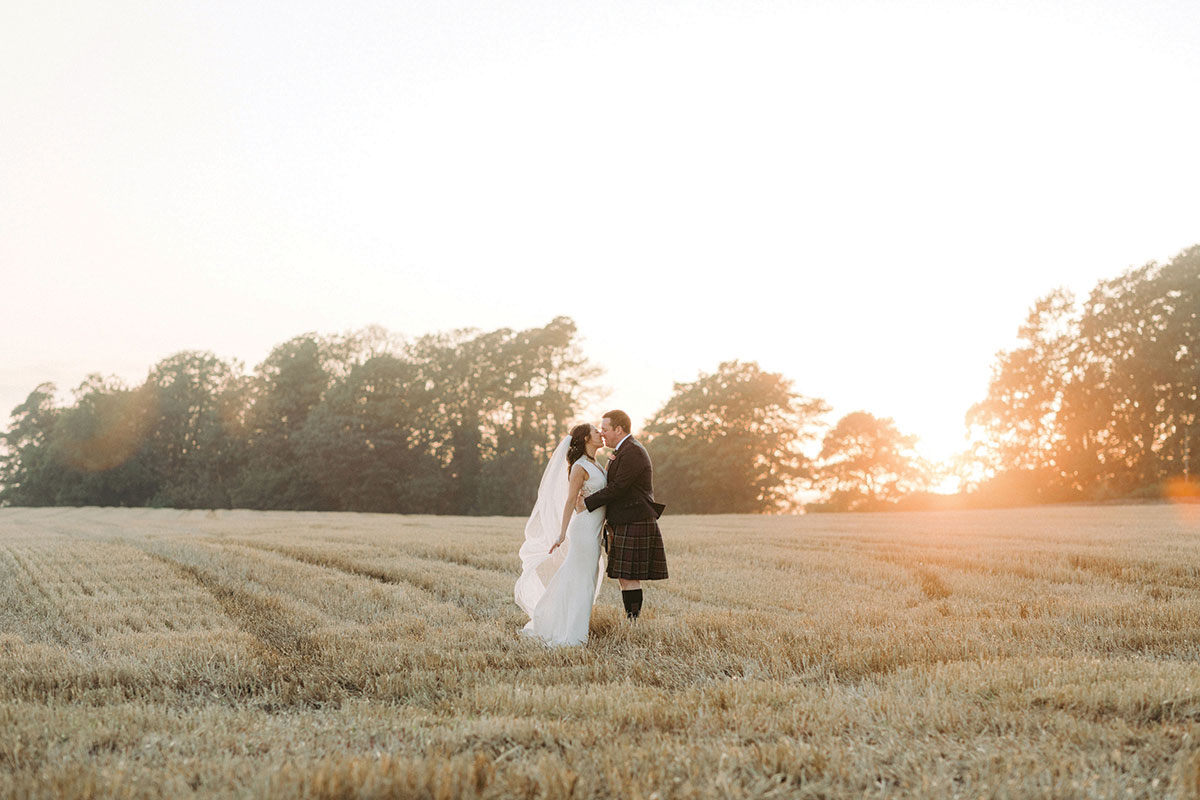 bride and groom kissing in a field of golden crops at sunset