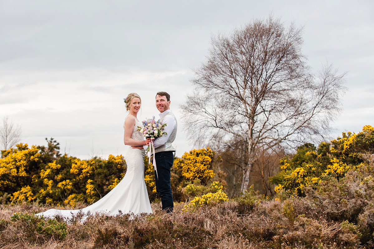 bride and groom posing on wedding day in Scottish countryside with gorse in background