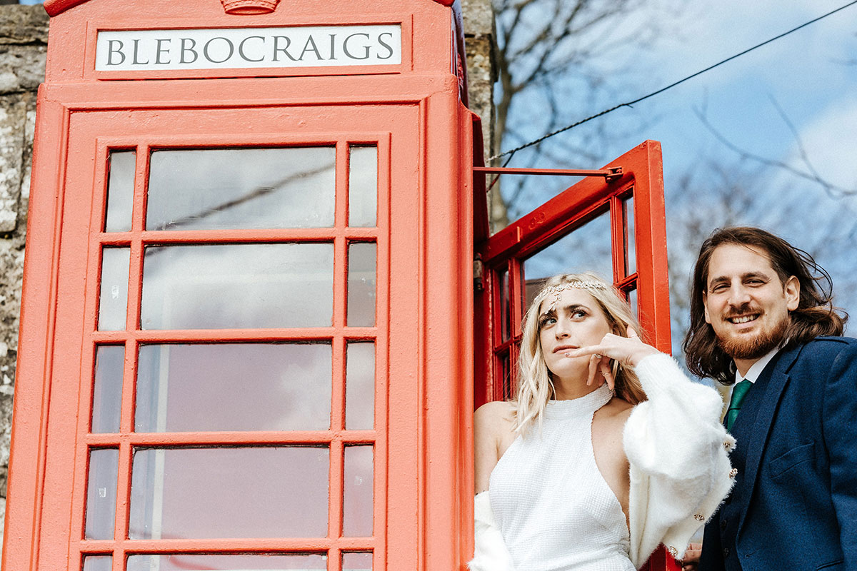 a bride and groom pose at a red phone box in Blebo Craigs in Fife