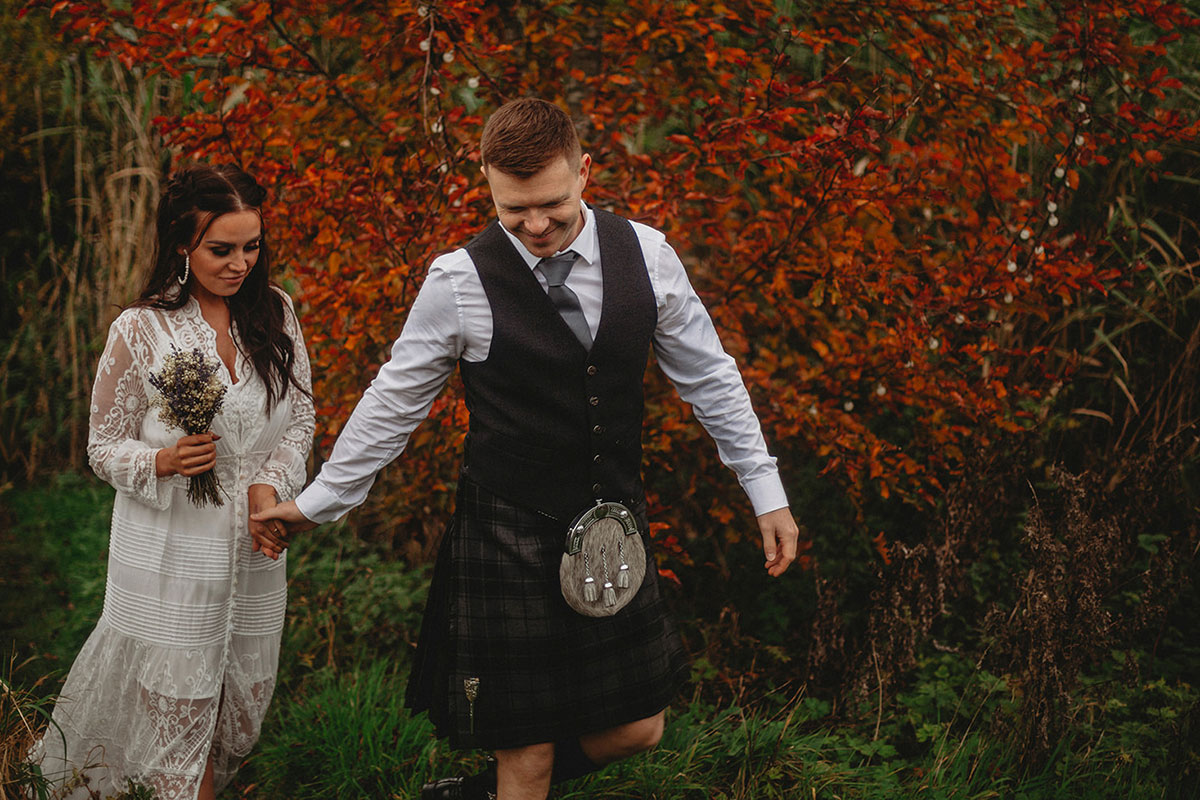 bride and groom walking with russet autumnal bush in background