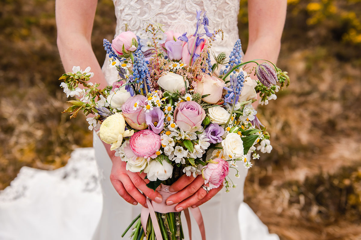 close up of bride carrying pastel bouquet by Bothy Blooms