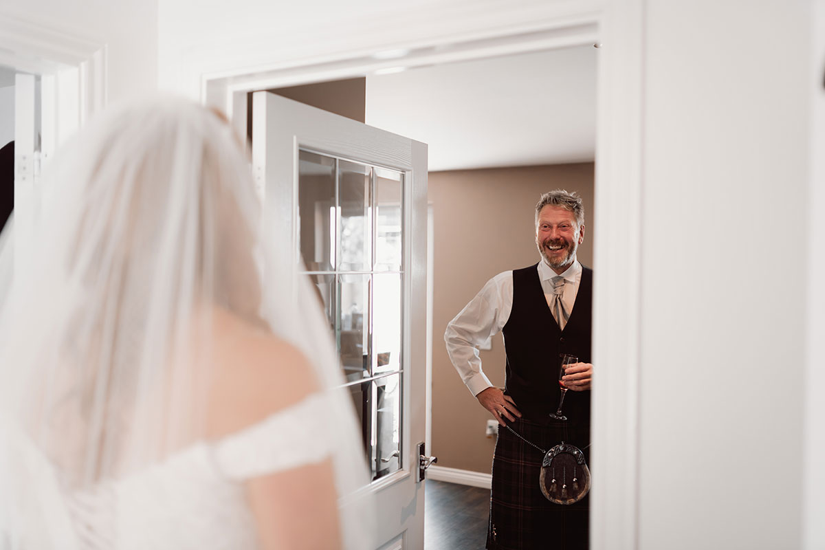 a man in a kilt smiling as a bride shows him her dress