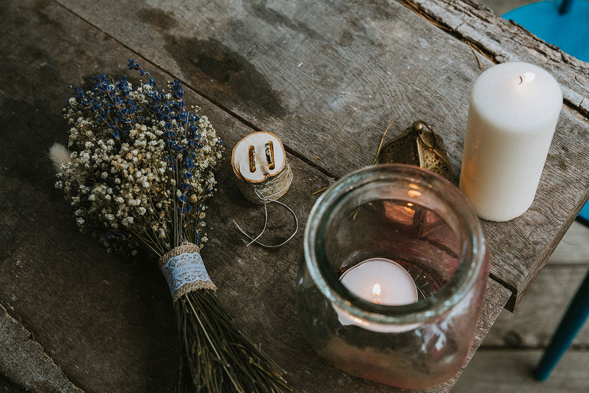 dried lavender bouquet, wedding rings and candles on a wooden top