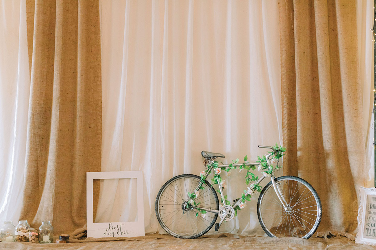 bike decorated with roses at a wedding with photo booth props