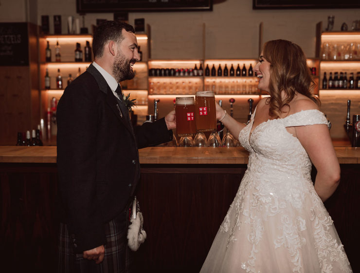 bride and groom drinking WEST beer and clinking glasses at a bar