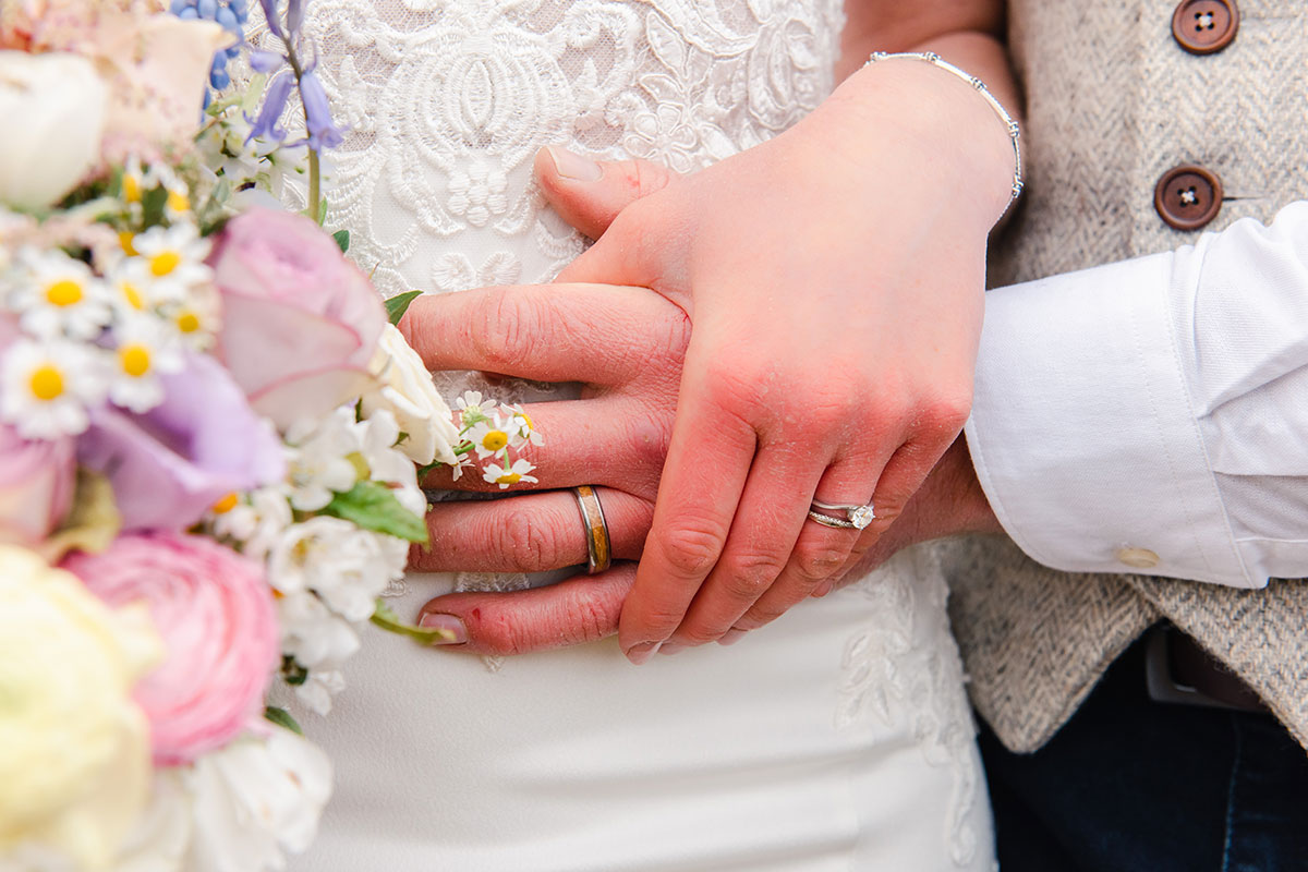 close up of bride and groom's hands and wedding rings with flowers in foreground