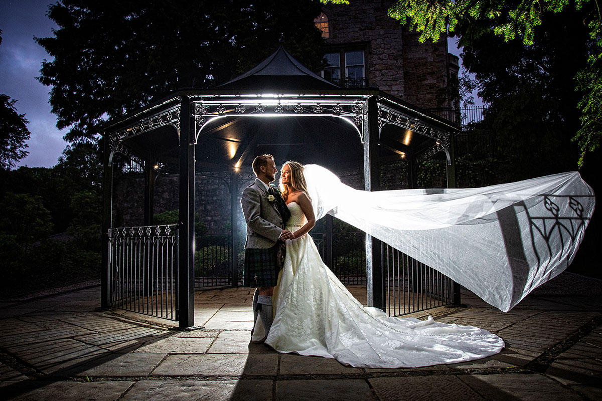 nighttime image of bride and groom in bandstand at Crossbasket Castle