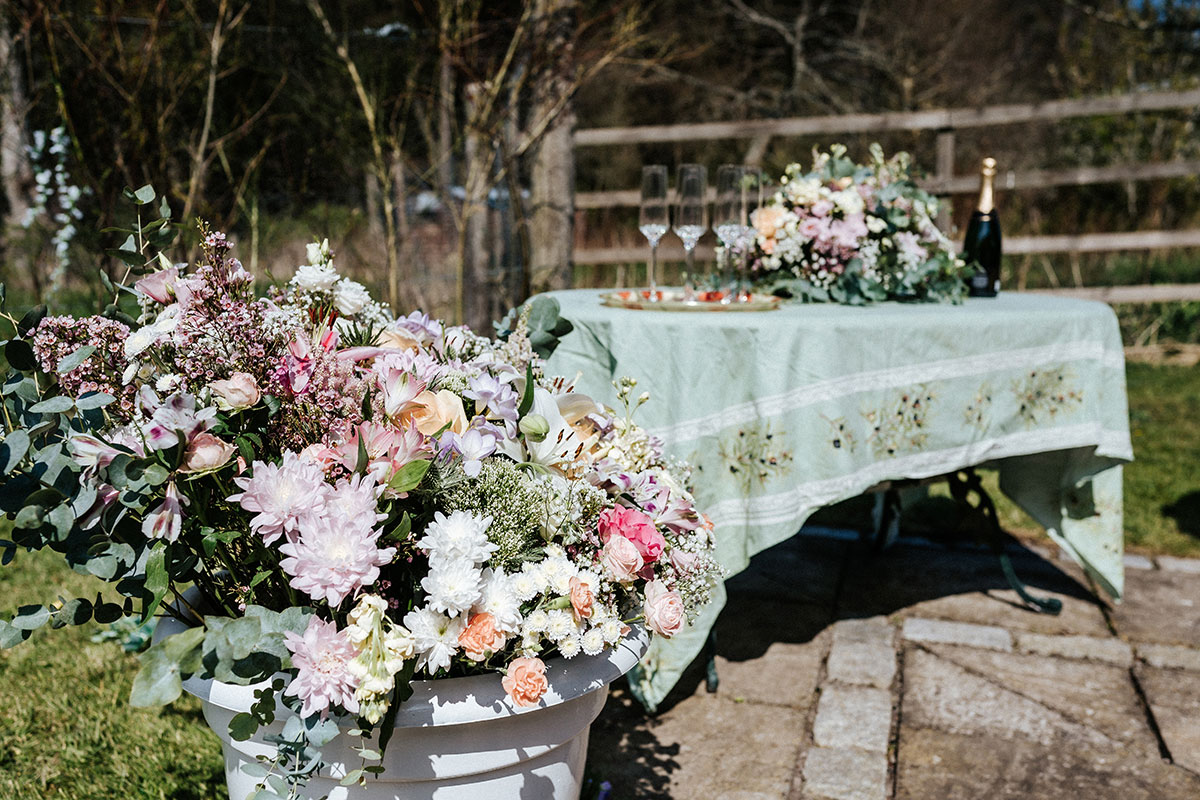 an urn filled with flowers and a table with a green table cloth and champagne glasses and bottle on top