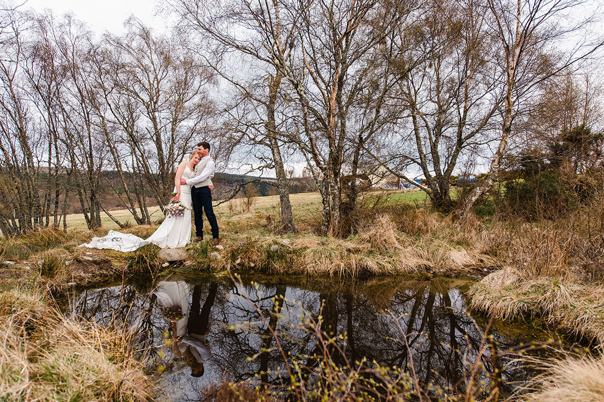 bride with head on groom's shoulder standing next to a pond and trees in Scotland