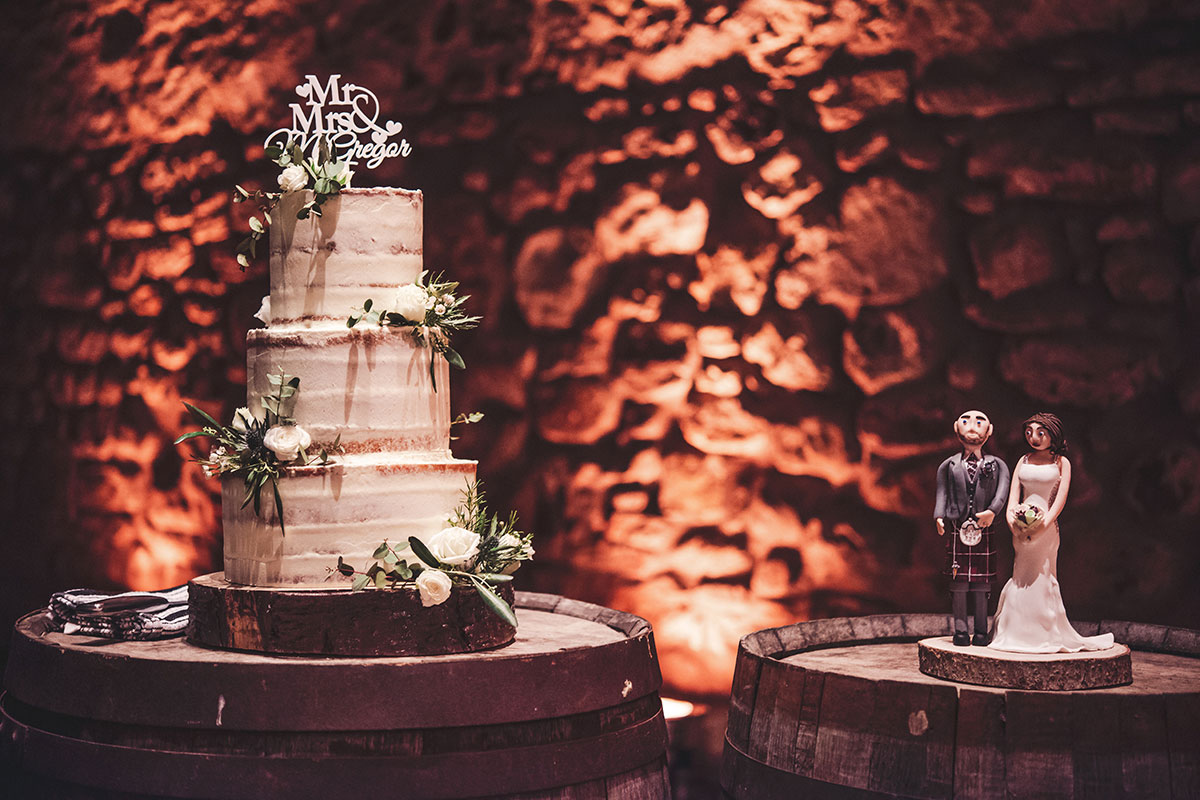 three tier wedding cake sitting on top of a wooden barrell with bride and groom figurine on another barrel