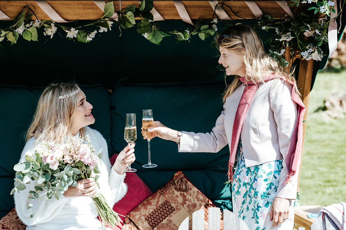 a sitting bride and a lady cheers champagne glasses together and smile at each other