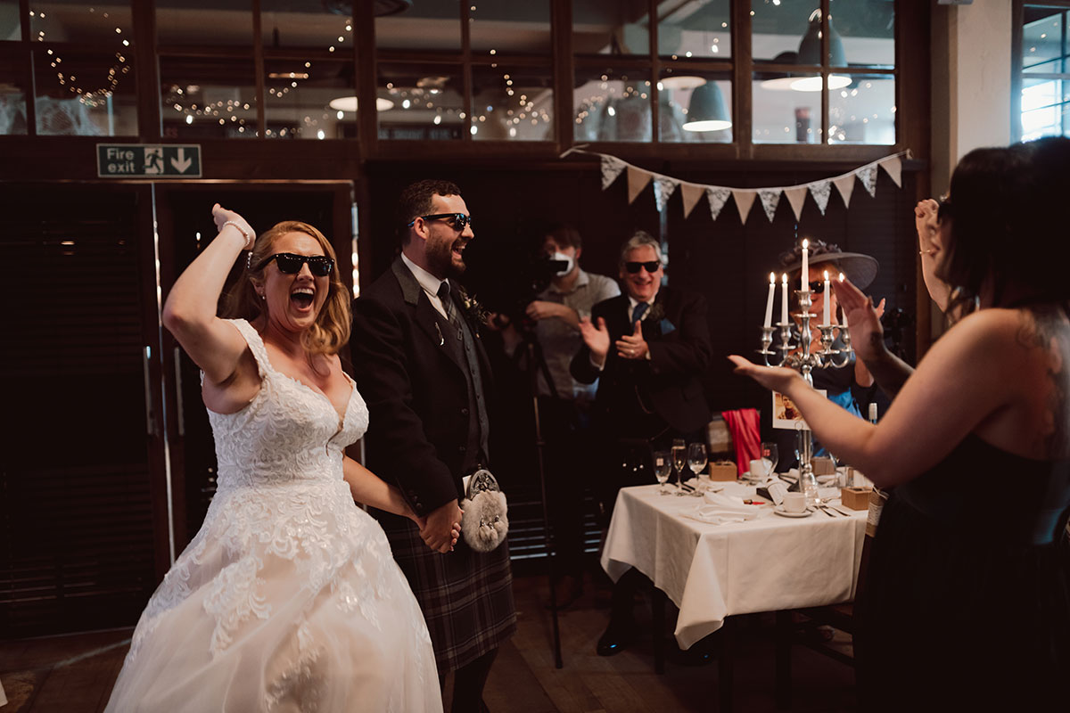 bride and groom entering wedding reception laughing at wearing dark sunglasses at West on the Green
