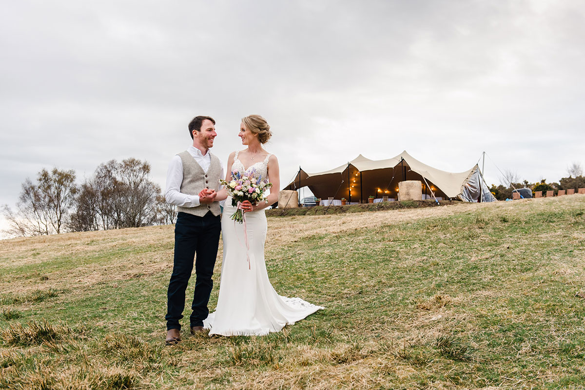 bride and groom smiling with Highland Stretch Tents tipi in background on hill