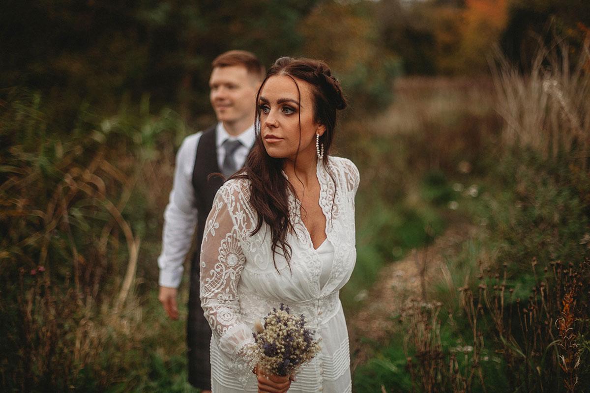 bride leading groom on walk in countryside