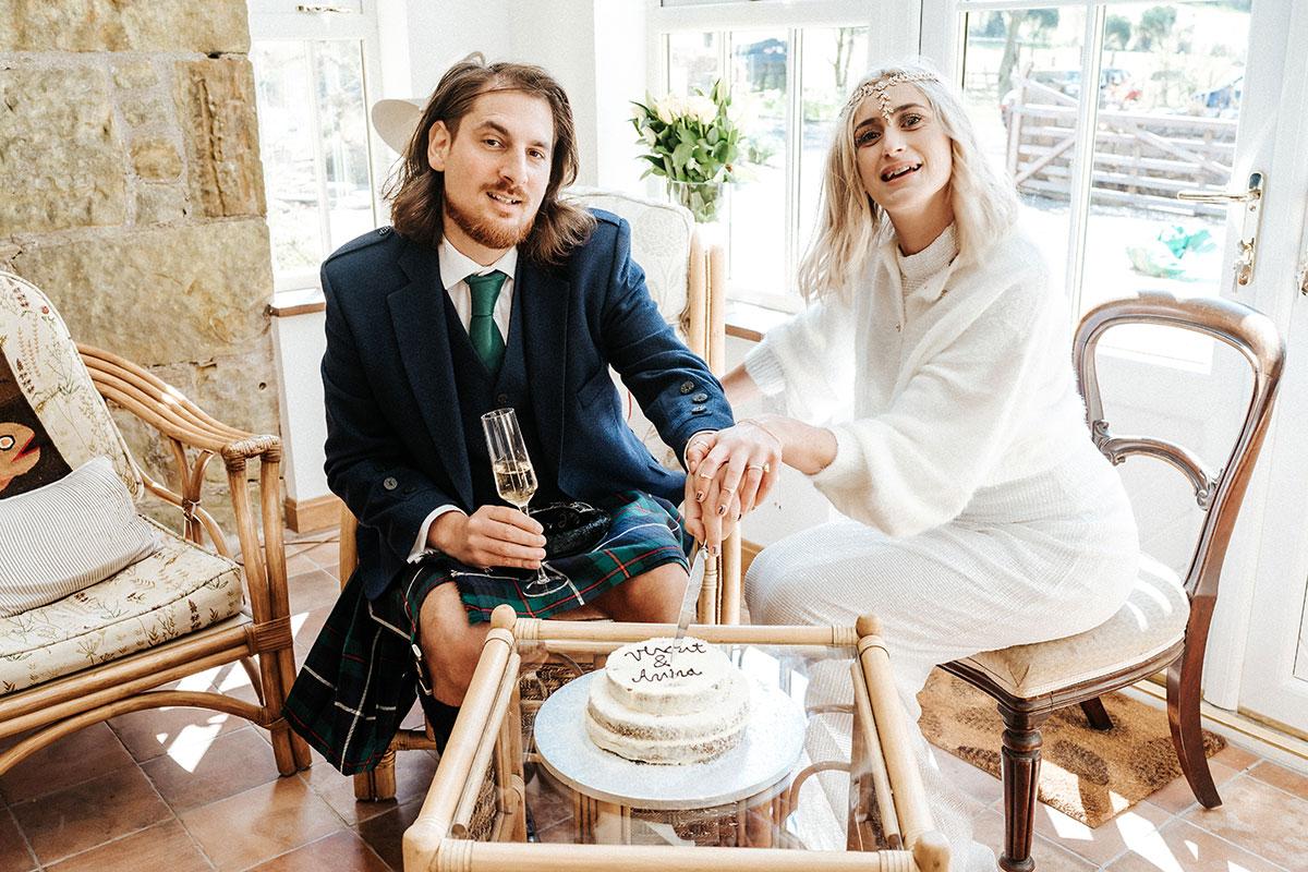 a bride and a groom sitting down cutting their wedding cake