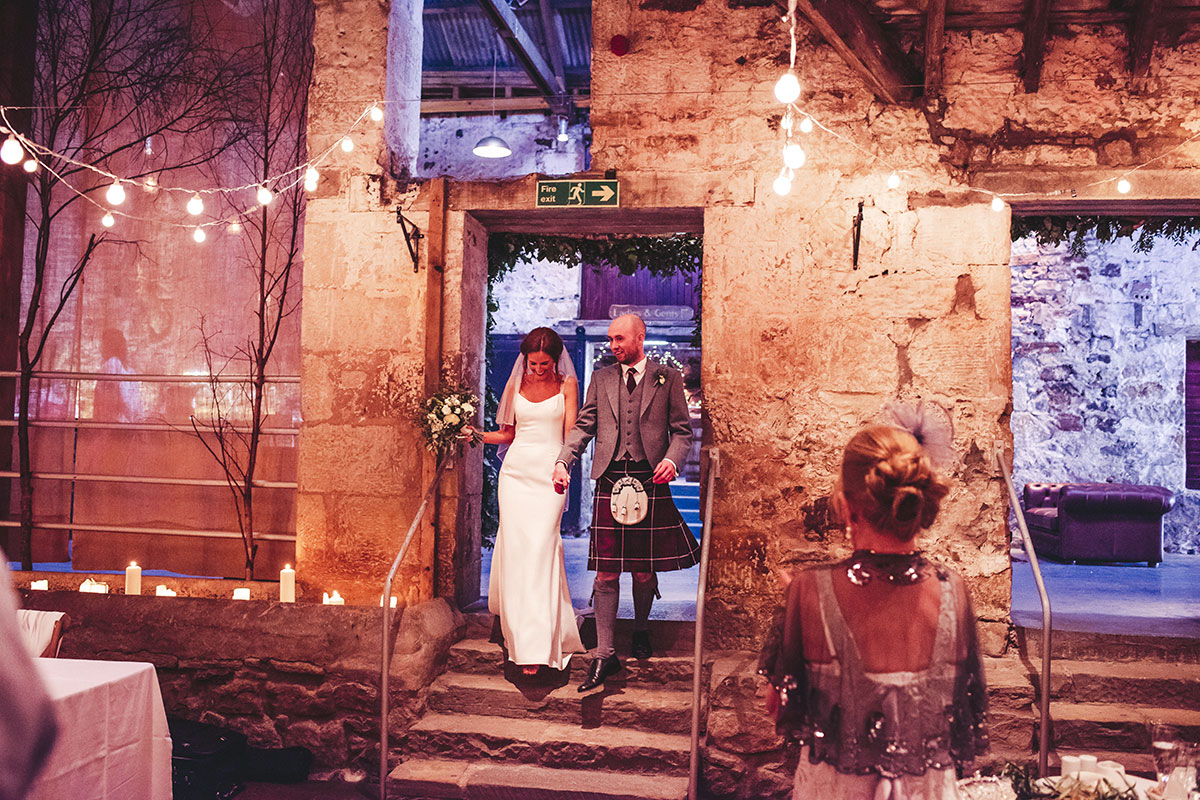 a bride and groom walking down stairs into a room at Kinkell Byre