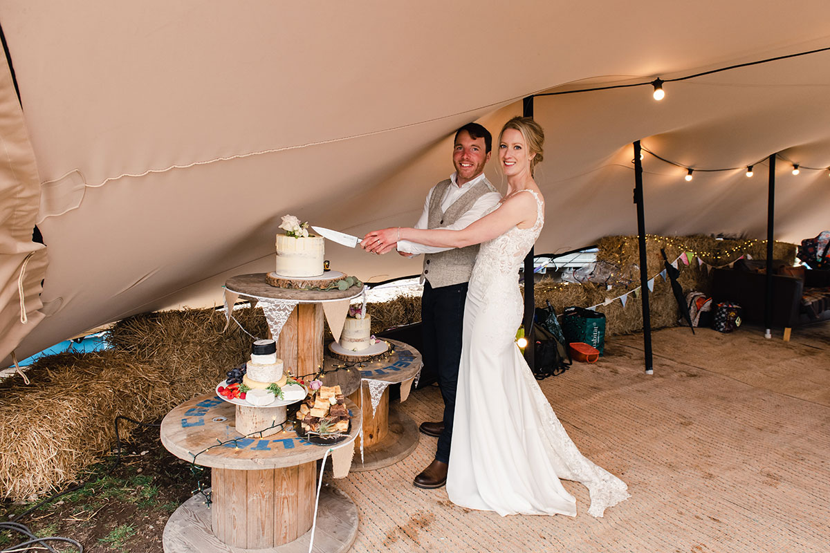 bride and groom smiling and cutting wedding cake in a tipi