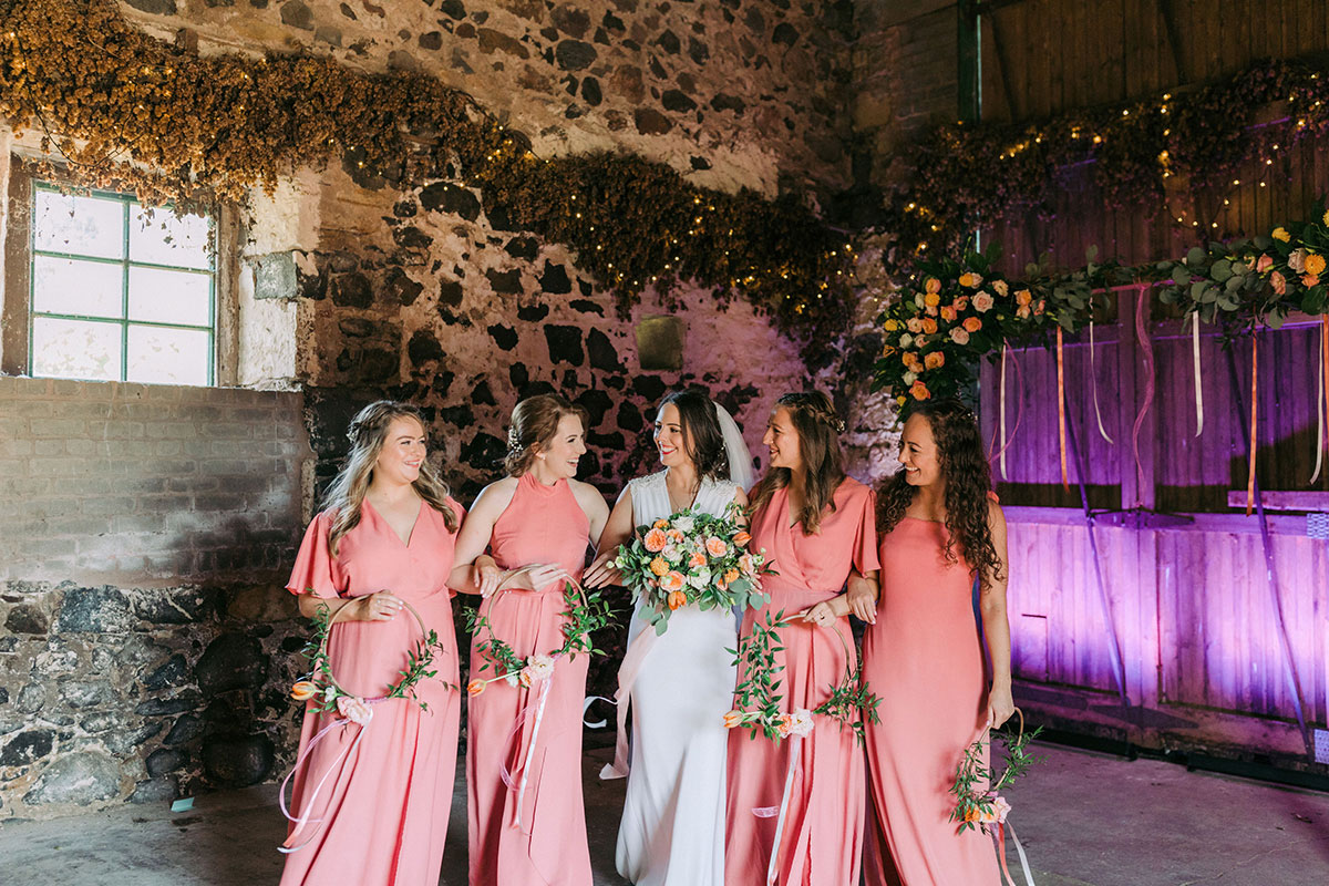 bride smiling with four bridesmaids wearing coral dresses at Pratis Barns