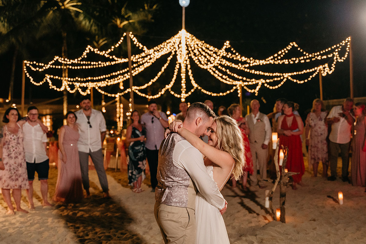 a bride and groom have a first dance at night on the beach at The Sarojin in Khao Lak in Thailand