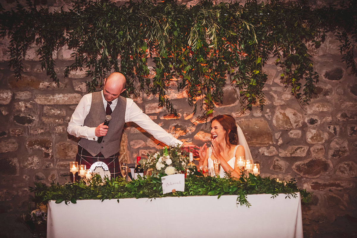 a groom laughing while touching a bride on her shoulder during his wedding speech with green foliage hanging in background