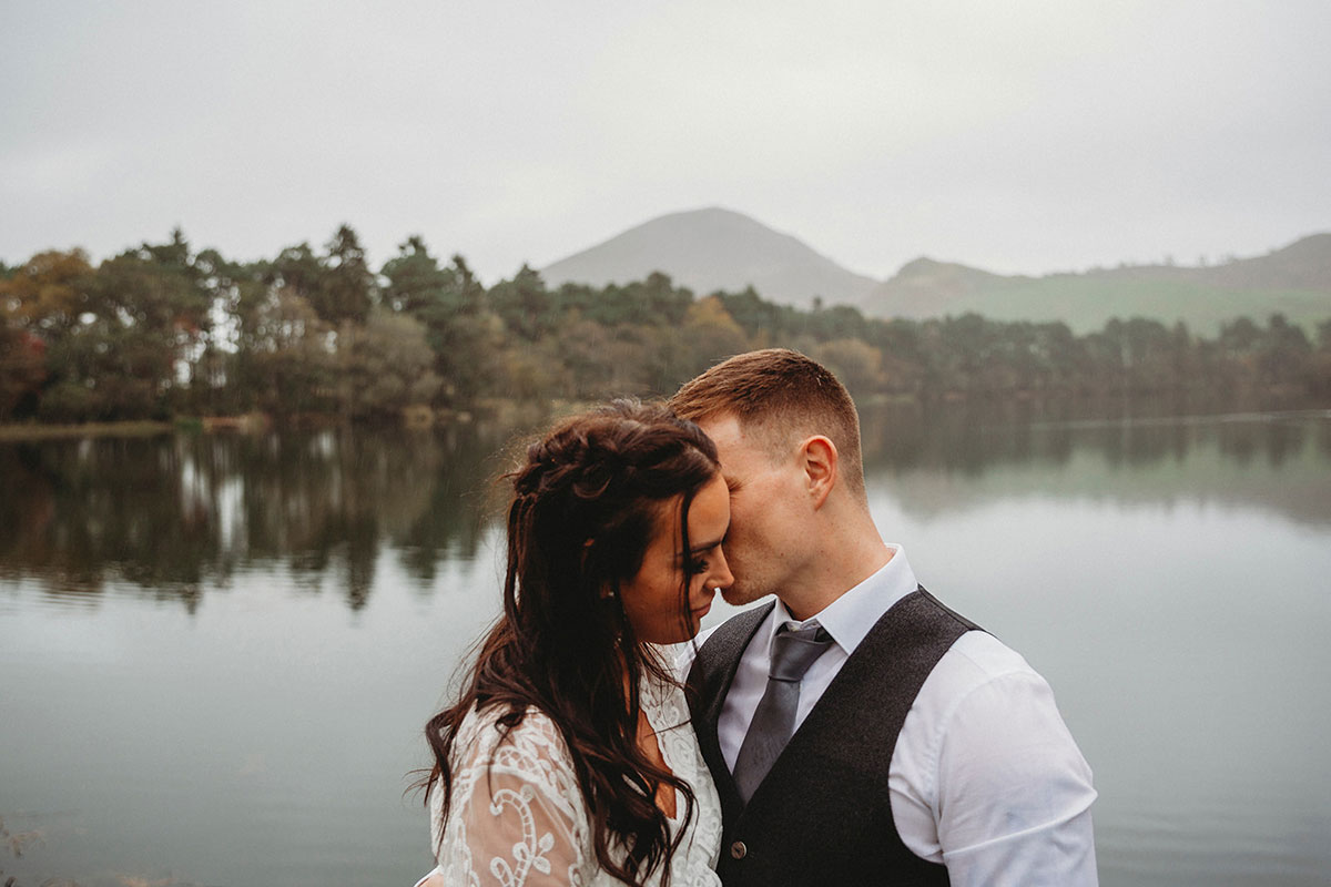 bride and groom kissing by loch in Scottish borders