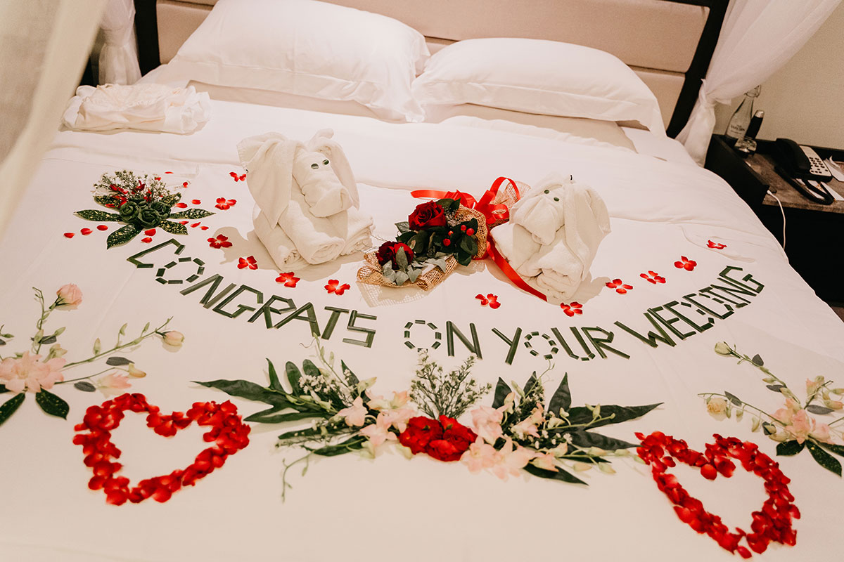 a bed decorated with red rose petals and leaves at The Sarojin in Khao Lak in Thailand