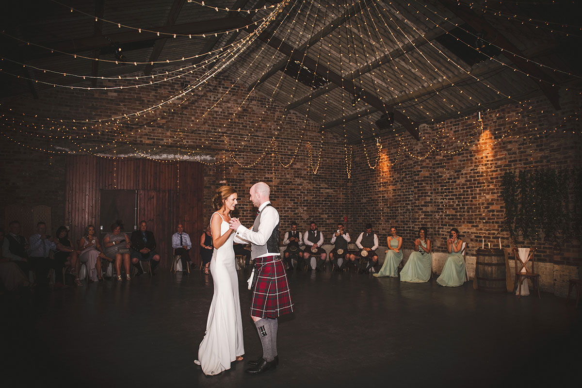 a bride and groom performing their first dance at Kinkell Byre while seated wedding guests look on