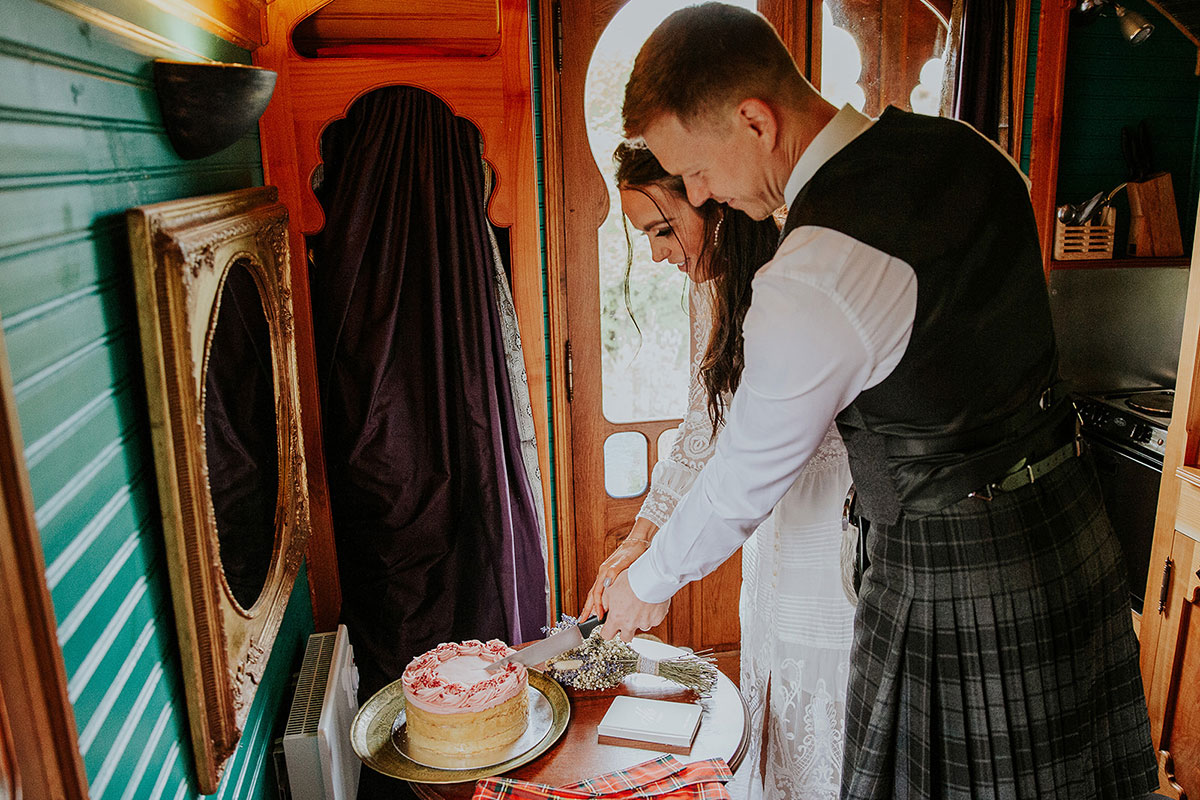 bride and groom cutting wedding cake in Roulotte Retreat