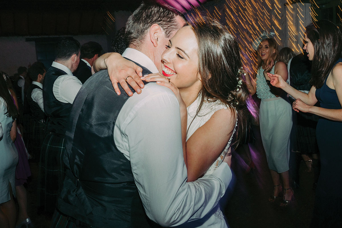 bride hugging groom surrounded by wedding guests