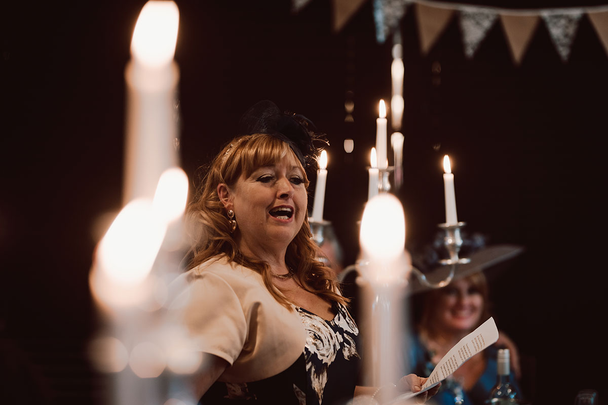 woman holding notes and speaking surrounded by candlelight