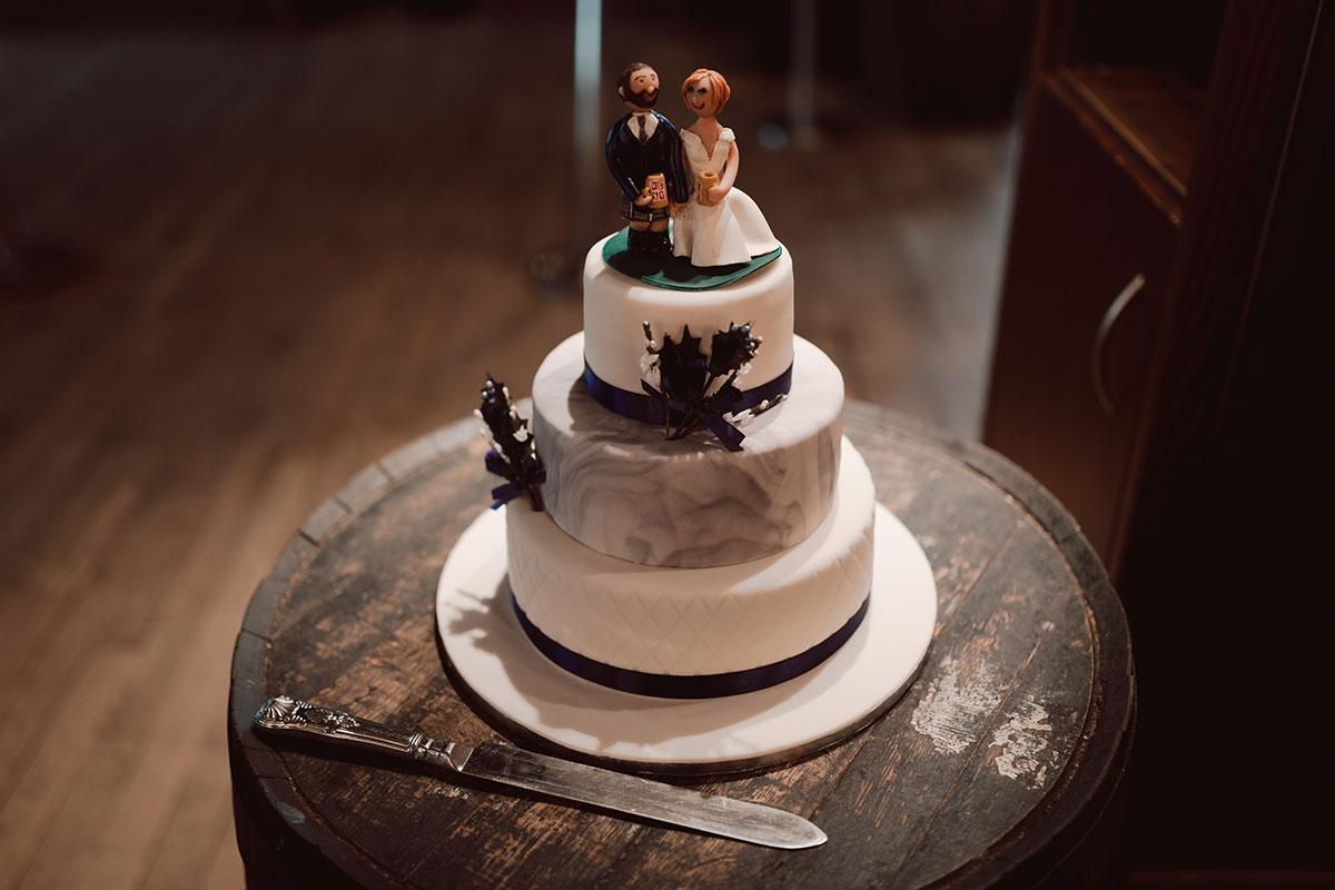 a three-tier wedding cake on a wooden barrell