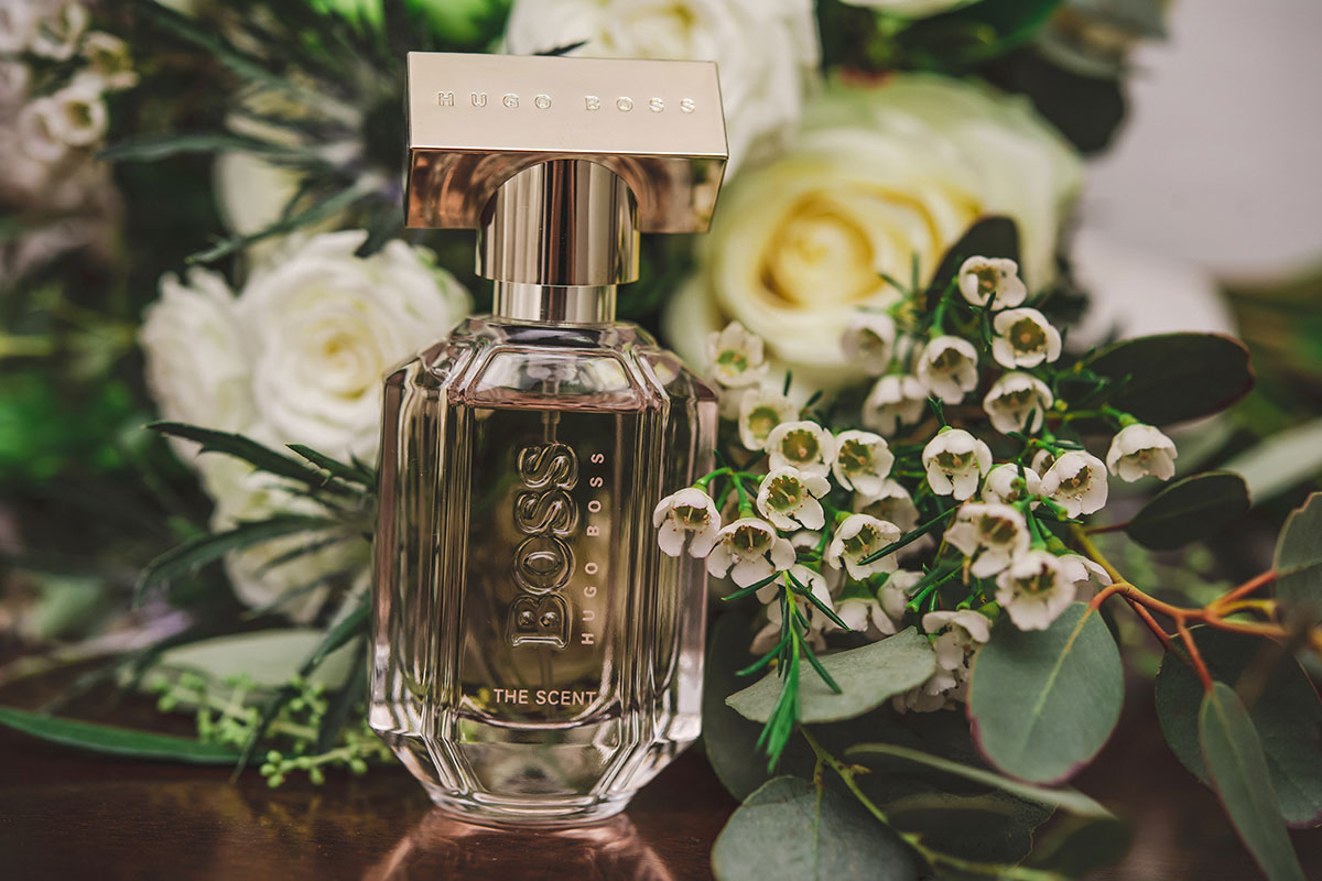 a glass bottle of hugo boss fragrance with flowers in background