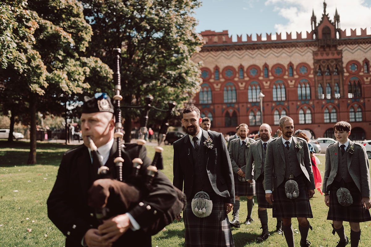 a group of men in kilts being piped across Glasgow Green with the Templeton Carpet Factory in background