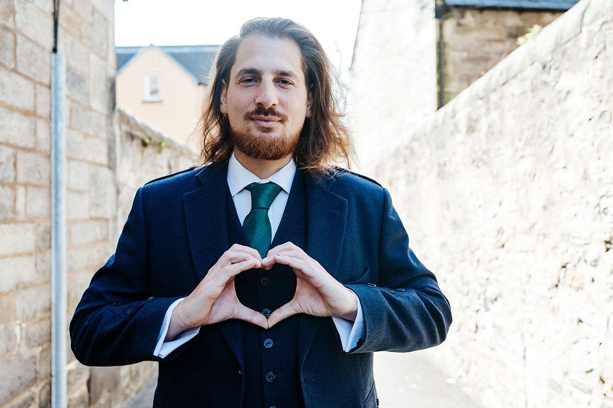 a man with a beard wearing a tie and suit jacket making a heart shape with his hands