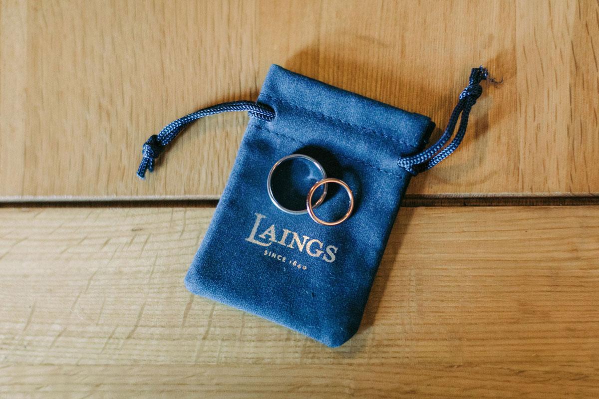 two wedding rings on blue Laings ring bag