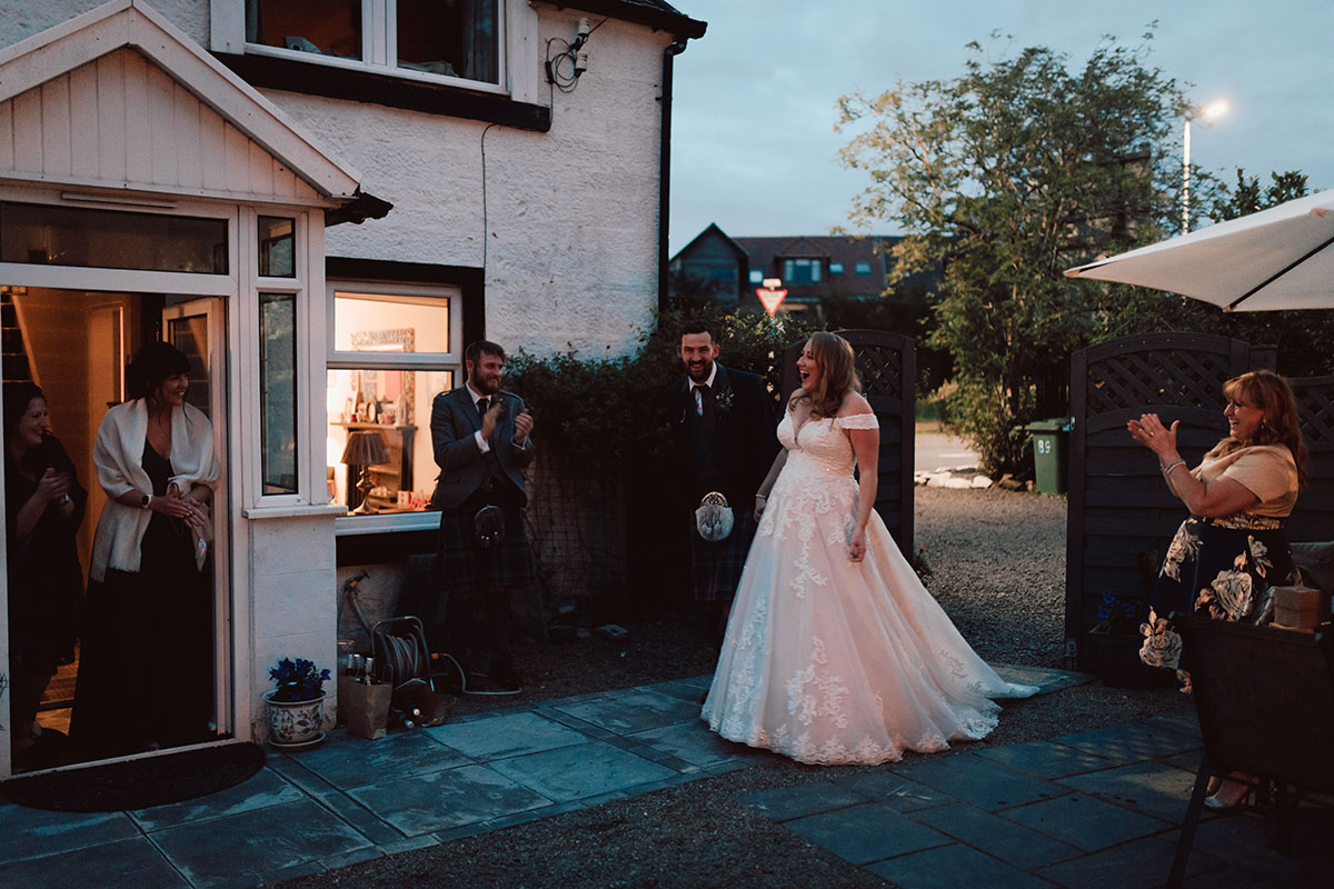 bride and groom standing in a garden surrounded by clapping guests