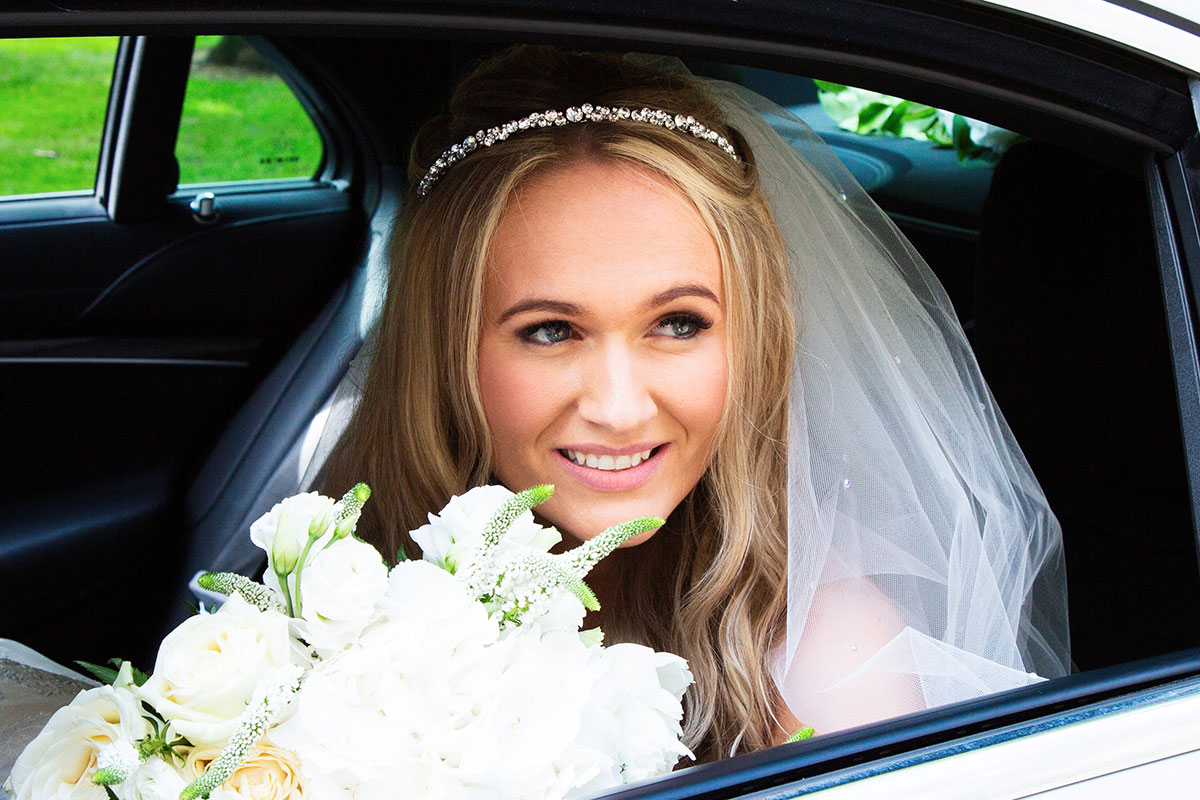 a bride looking out of a car window carrying a bouquet of flowers