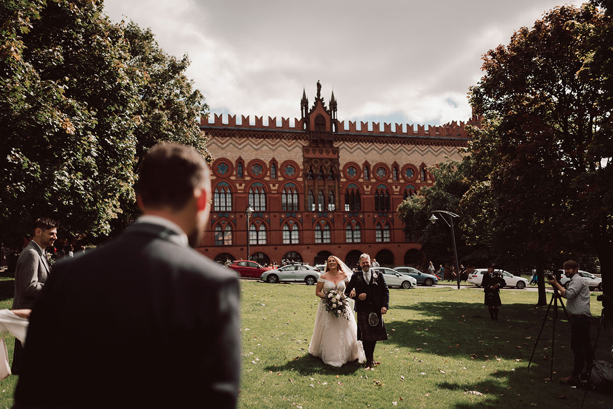 a wedding ceremony outside on Glasgow Green with the Templeton Carpet Factory in background