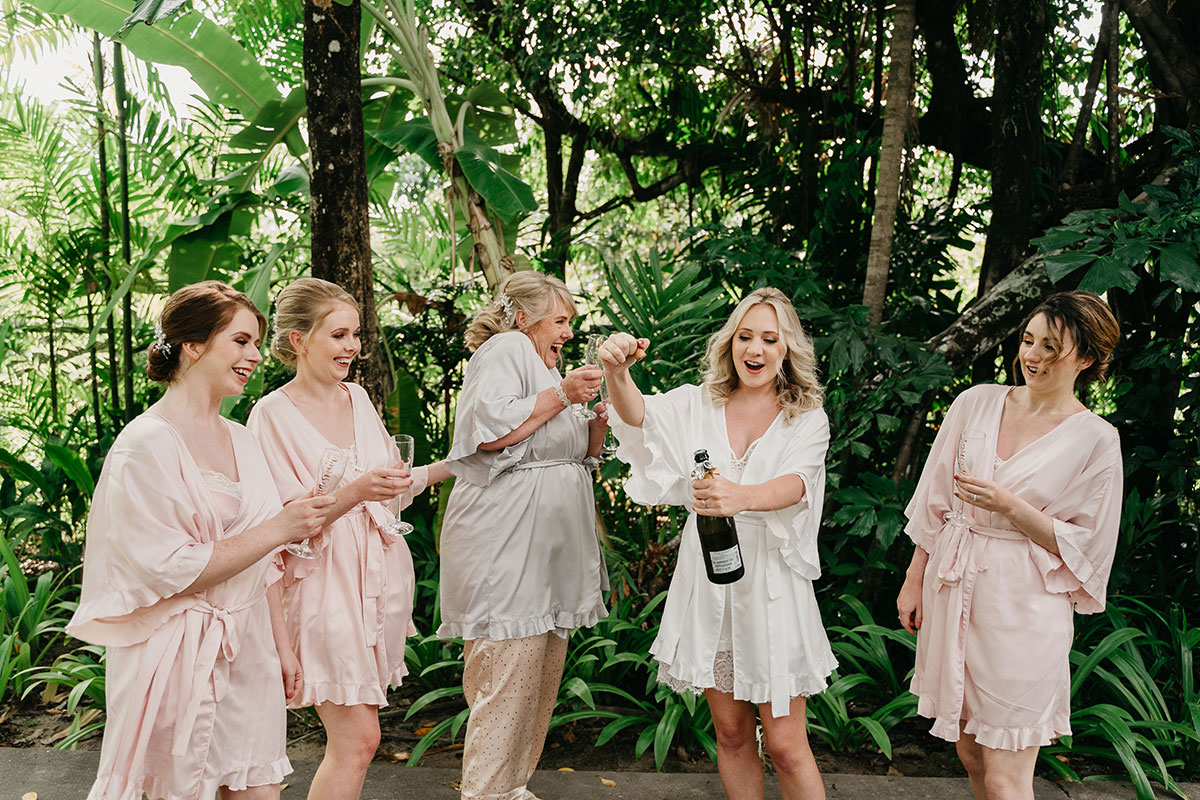 bride, bride's mum and 3 bridesmaids wearing robes and popping champagne with tropical trees in background