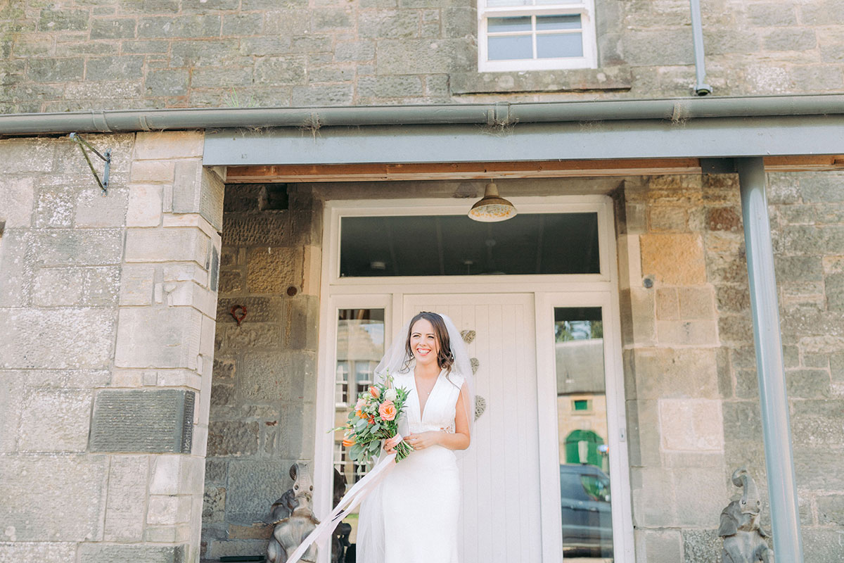 bride smiling standing outside a stone building