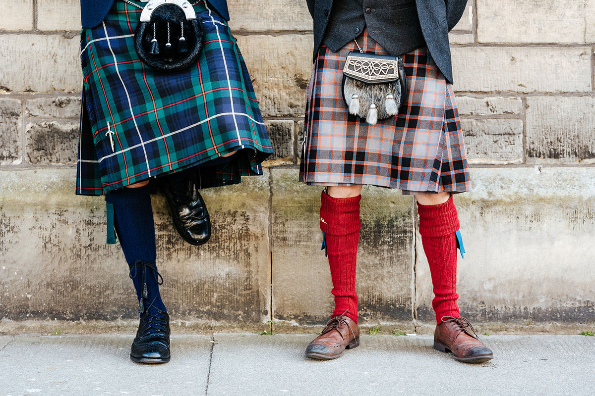 the bottom half of two men wearing kilts posing against a wall