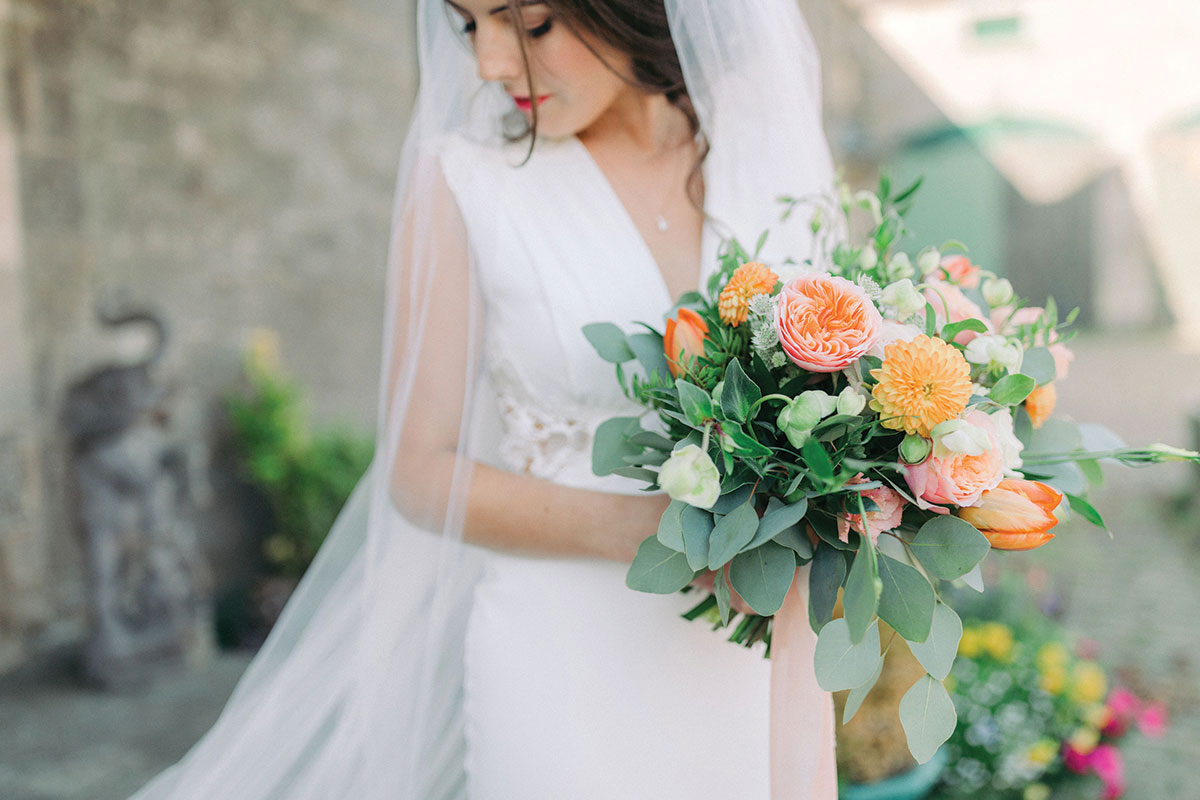 a dark-haired bride looking down holding bouquet by Pretty Little Flowers