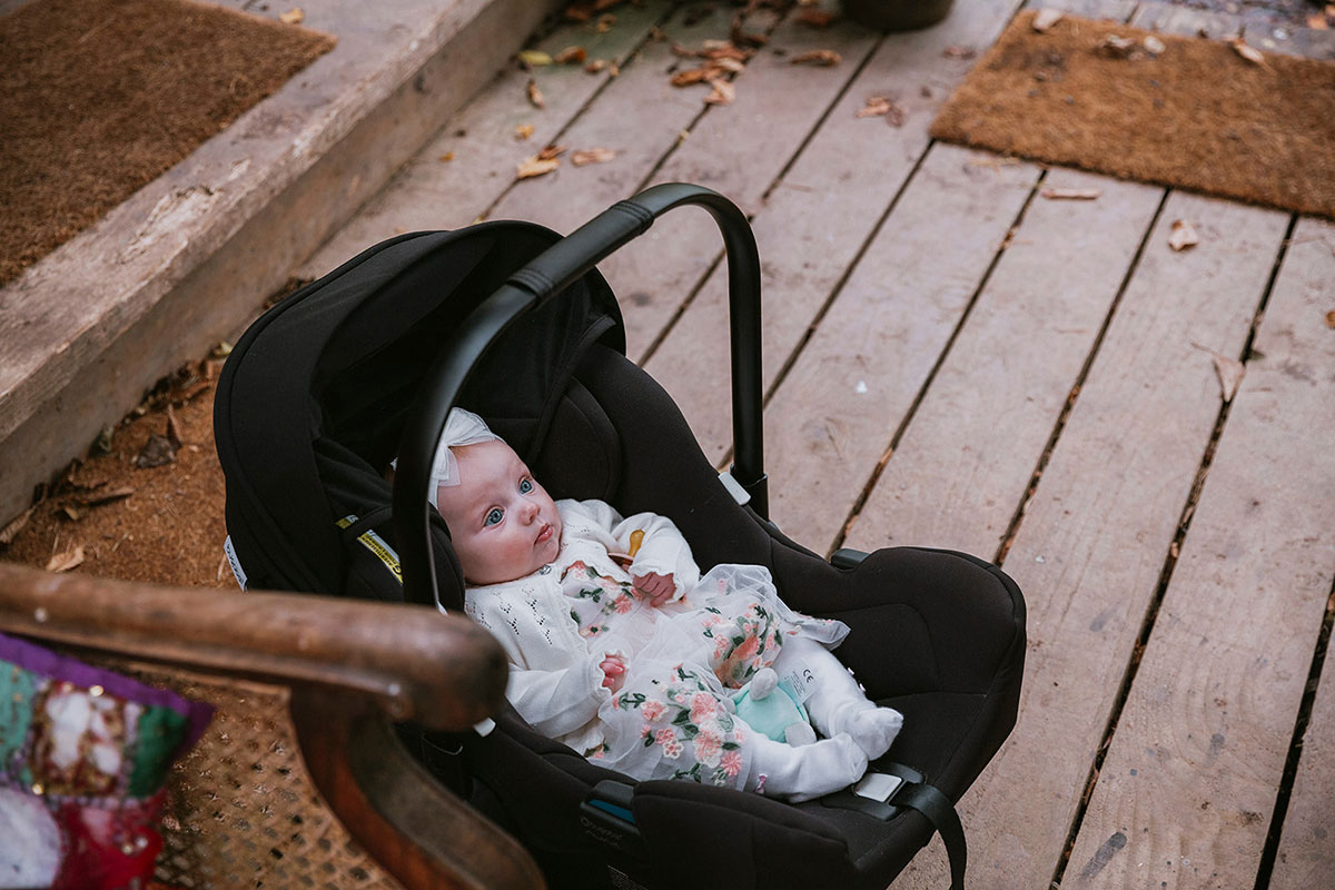 baby wearing floral dress in a black baby carrier seat