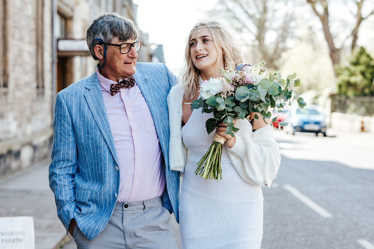 bride being hugged by man wearing blue pinstripe jacket in a street in St Andrews
