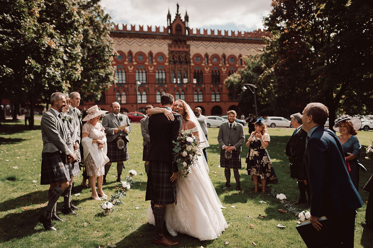 bride hugging a groom at an outdoor wedding ceremony on Glasgow Green