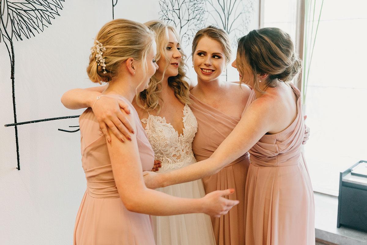a bride hugging her 3 bridesmids