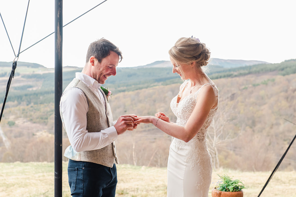 bride and groom exchanging wedding rings with countryside in background